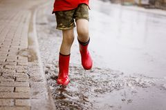 Enfant portant les bottes rouges de pluie sautant dans un magma Fin vers le haut Enfant ayant l'amusement avec l'éclaboussement a photos libres de droits
