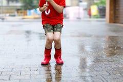 Enfant portant les bottes rouges de pluie sautant dans un magma Fin vers le haut Enfant ayant l'amusement avec l'éclaboussement a image stock