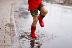 Enfant portant les bottes rouges de pluie sautant dans un magma Fin vers le haut Enfant ayant l'amusement avec l'éclaboussement a images libres de droits