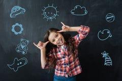 Enfant positif faisant des visages tout en ayant l'amusement à la partie Photos libres de droits