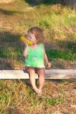 Enfant pour manger l'épi de maïs sur le banc Photos stock