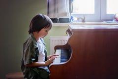 Enfant préscolaire, garçon mignon, jouant le piano à la maison Photographie stock libre de droits