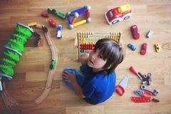 Enfant préscolaire, jouant avec l'abaque et d'autres jouets, se reposant dessus Photos libres de droits