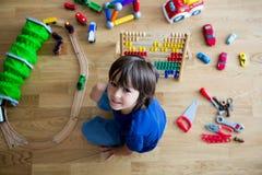 Enfant préscolaire, jouant avec l'abaque et d'autres jouets, se reposant dessus Image libre de droits