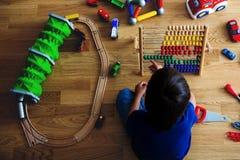 Enfant préscolaire, jouant avec l'abaque et d'autres jouets, se reposant dessus Photographie stock libre de droits