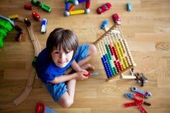 Enfant préscolaire, jouant avec l'abaque et d'autres jouets, se reposant dessus Image stock