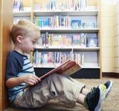 Enfant préscolaire lisant un livre à la bibliothèque Image stock