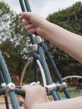 Enfant prêt à monter le filet de bousculade de terrain de jeu Images stock