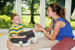 Enfant prêt à rire tandis que pied chatouillé par la fille Images stock