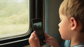 Enfant prenant des photos de téléphone portable dans le train banque de vidéos