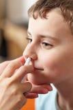 Enfant prenant une dose de jet nasal Images libres de droits
