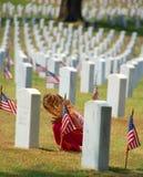 Enfant priant dans le cimetière Photographie stock