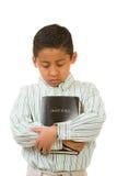 Enfant priant tout en étreignant la bible Image stock