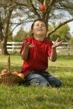 Enfant projetant vers le haut une pomme Image libre de droits