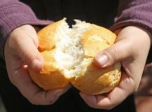 Enfant qui casse une partie de pain avec des mains Images stock