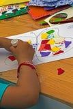 Enfant qui colle ensemble des morceaux de papier coloré photo libre de droits