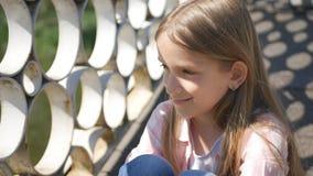 Enfant réfléchi en parc, petite fille songeuse extérieure, sourire triste sur le visage d'enfant photos libres de droits