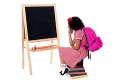 Enfant réfléchi s'asseyant devant le tableau noir Photos libres de droits