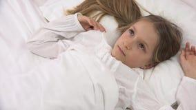 Enfant réfléchi triste dans le lit ne dormant pas, visage songeur éveillé de fille dans la chambre à coucher banque de vidéos