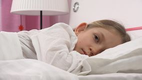 Enfant réfléchi triste dans le lit ne dormant pas, visage songeur éveillé de fille dans la chambre à coucher 4K clips vidéos