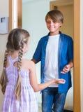 Enfant recevant l'intérieur prévu d'ami à la maison Photo stock