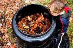 Enfant regardant dans le coffre de compost Photographie stock libre de droits