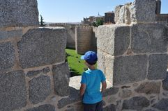 Enfant regardant des murs d'Avila, Espagne photographie stock