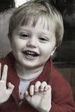 Enfant regardant fixement à l'extérieur l'hublot Photographie stock libre de droits