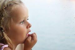 Enfant regardant hors de l'hublot Images libres de droits