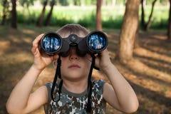 Enfant regardant par des jumelles Images stock