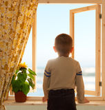 Enfant regardant par la fenêtre ouverte Photo libre de droits