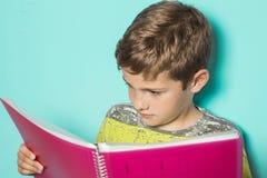 Enfant regardant un carnet de devoirs images stock