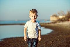 Enfant riant élégant courant le long du bord de la mer image stock