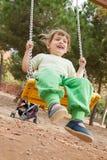 Enfant riant au terrain de jeu dans le jour d'été ensoleillé Image libre de droits