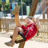 Enfant riant dans les dres rouges sur l'oscillation à chaînes Image libre de droits