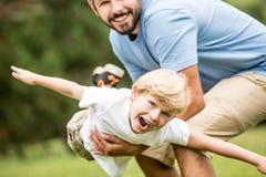 Enfant riant et jouant avec le père Images stock
