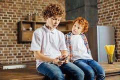 Enfant roux adorable regardant un frère plus âgé écoutant la musique Photo libre de droits