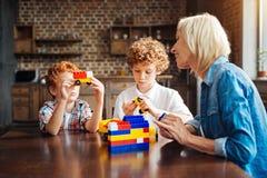 Enfant roux montrant le jouet de voiture à sa grand-maman Images stock