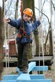 Enfant s'élevant dans la cour de jeu d'aventure. Photographie stock libre de droits