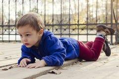 Enfant s'étendant sur l'extérieur au sol Image stock