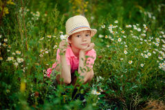 Enfant s'étendant sur l'herbe avec des marguerites Photographie stock libre de droits