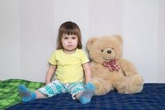 Enfant s'asseyant avec jouet d'ours de nounours le grand, concept d'amitié d'enfance Image libre de droits