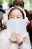 Enfant s'asseyant avec le livre devant le visage Photographie stock