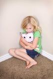 Enfant s'asseyant dans le coin photo stock