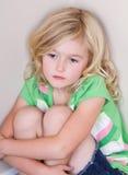 Enfant s'asseyant dans le coin photos stock