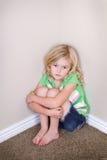 Enfant s'asseyant dans le coin photo libre de droits