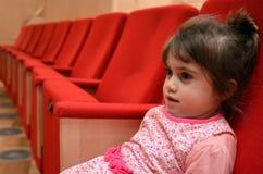 Enfant s'asseyant dans le hall de cinéma Photographie stock