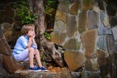 Enfant s'asseyant sur des étapes Photos libres de droits