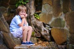 Enfant s'asseyant sur des étapes Image libre de droits
