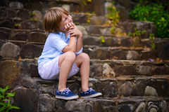 Enfant s'asseyant sur des étapes Photographie stock libre de droits